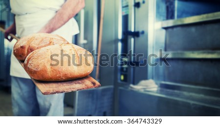 Baker in bakery with bread on shovel standing in front of oven, filtered image - stock photo