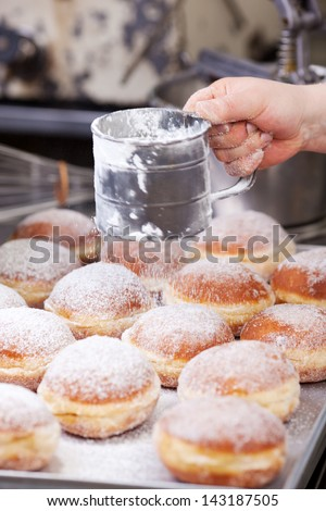 Baker is poring powdered sugar over doughnuts - stock photo