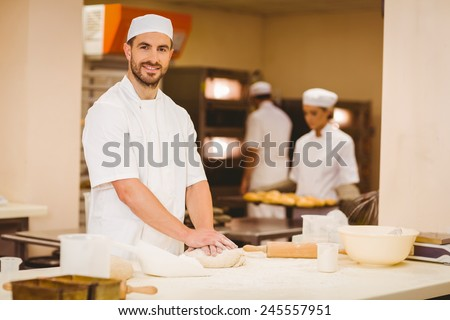 Baker kneading dough at a counter in a commercial kitchen - stock photo