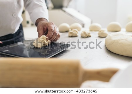 Baker kneading dough in a bakery. Bakery Concept. - stock photo