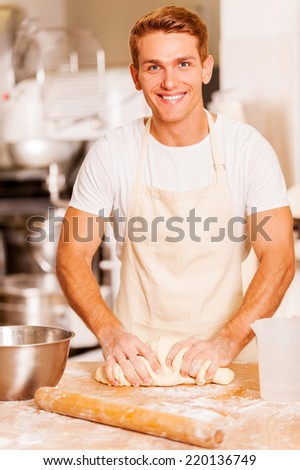 Baker kneading the dough. Cropped image of male baker kneading the dough  - stock photo