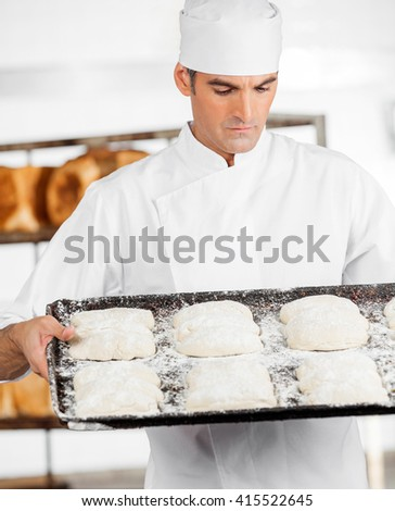 Baker Looking At Dough In Baking Tray