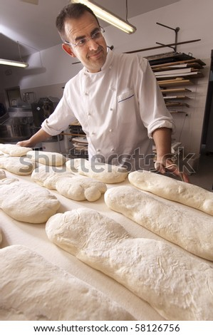 Baker makes the bread dough in the oven for baking - stock photo