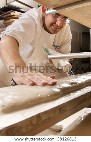 Baker makes the bread dough on the baking sheet in the oven to bake - stock photo
