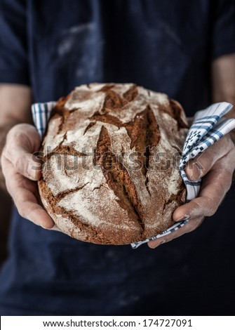 Baker man holding rustic organic loaf of  bread in hands - rural bakery. Natural light, moody background with free text space good for poster or cover. - stock photo