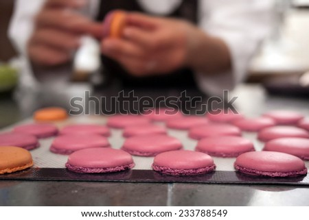 Baker placing macaron cookies on sheet for baking, with baker blurred ...