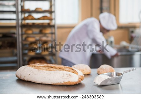 Baker preparing dough in industrial mixer at the bakery - stock photo