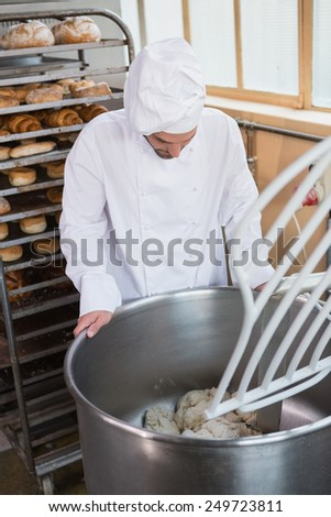 Baker preparing dough in industrial mixer at the bakery