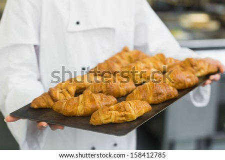 Baker presenting some croissants on a baking tray - stock photo