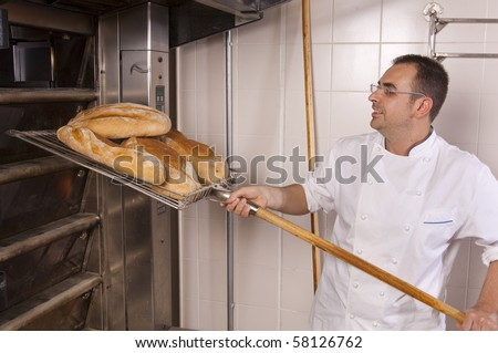 Baker removed from the oven freshly baked bread - stock photo