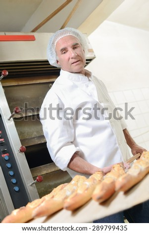 Baker removing bread from oven - stock photo