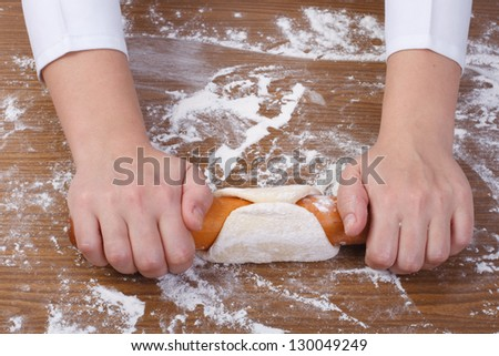 baker rolls out the dough on a wooden kitchen table sprinkled with flour - stock photo