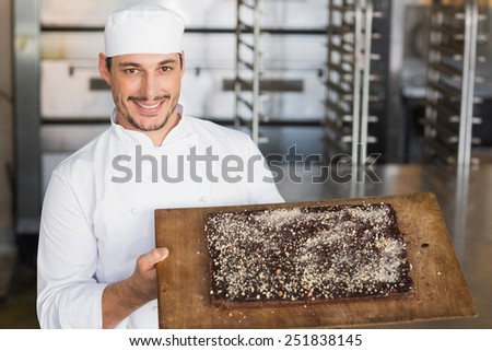 Baker showing freshly baked brownie in the kitchen of the bakery - stock photo