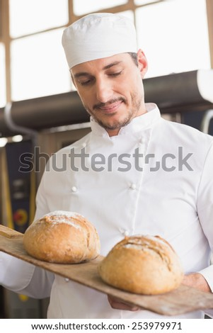 Baker showing tray of fresh bread in the kitchen of the bakery - stock photo