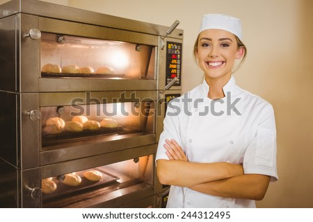 Baker smiling at camera beside oven in a commercial kitchen - stock photo