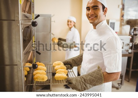Baker smiling at camera taking rolls out of oven in a commercial kitchen - stock photo