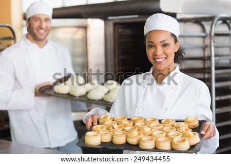 Baker smiling at the camera holding tray in the kitchen of the bakery - stock photo
