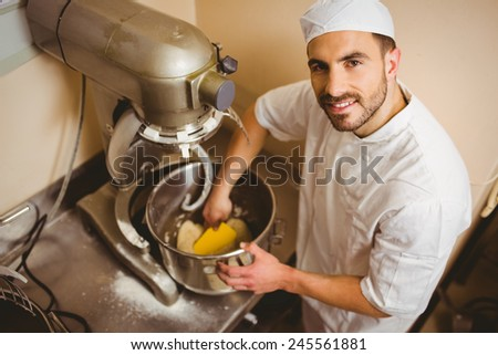 Baker using large mixer to mix dough in a commercial kitchen
