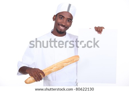 Baker with a baguette and a board left blank for your message - stock photo