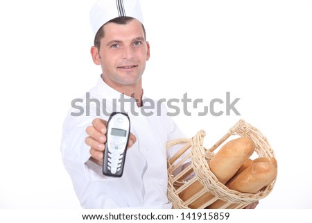 Baker with basket and phone - stock photo