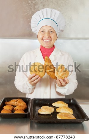 Baker with fresh pastries at bakery - stock photo
