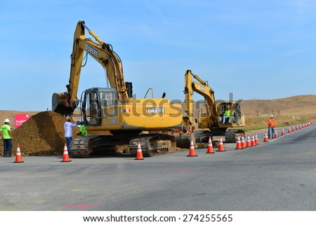 BAKERSFIELD, CA - APR 29, 2015: Traffic must be managed while heavy equipment is employed to lay new sewer pipe across busy State Route 178. - stock photo