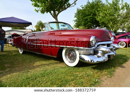 BAKERSFIELD, CA-APRIL 19, 2014: A very pretty maroon 1953 Cadillac convertible vies for attention among all the cars at the Cruisin' For A Wish Car & Motorcycle Show. - stock photo