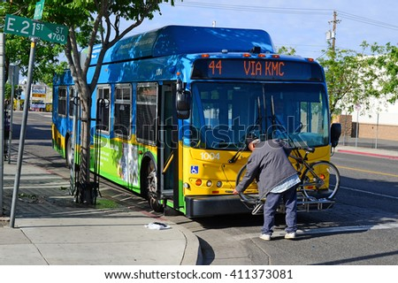 BAKERSFIELD, CA - APRIL 23, 2016: An unidentified commuter takes his bicycle off the rack furnished on every Golden Empire Transit bus, to continue his journey on two wheels. - stock photo
