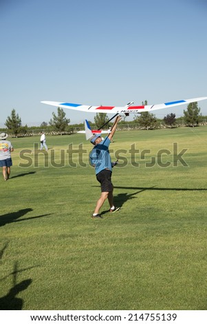 BAKERSFIELD, CA-AUGUST 24, 2014: Alex Ekemenko powers the electric winch with his foot as he launches his sailplane in the monthly contest hosted by the Southern San Joaquin Soaring Society. - stock photo