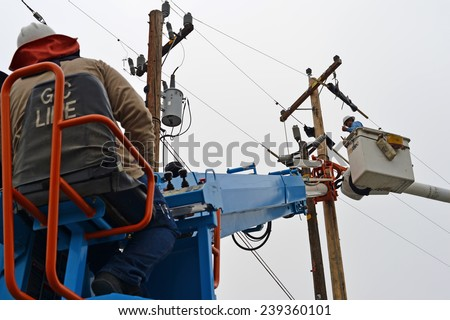 BAKERSFIELD, CA - DECEMBER 21, 2014: An electrician works from the basket of a man lift during the high voltage cutover phase of a wood pole replacement by the local utility company. - stock photo