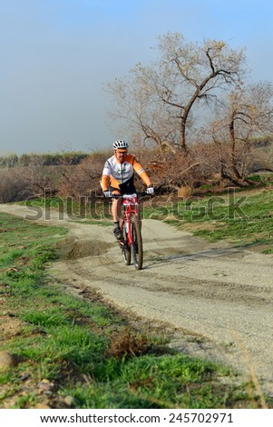 BAKERSFIELD, CA - JAN 17, 2015: An unidentified male rider negotiates the dirt and mud trails on the course of the Rio Bravo Rumble biathlon (running and mountain biking). - stock photo