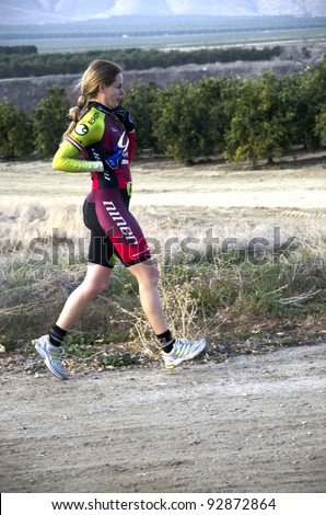 BAKERSFIELD, CA - JAN 14: An unidentified woman runs the dirt cross country leg of the Rio Bravo Rumble biathlon (running and mountain biking) on January 14, 2012, in Bakersfield, California. - stock photo
