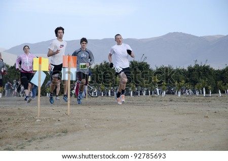 BAKERSFIELD, CA - JAN 14: Contestants run the dirt path cross country leg of the Rio Bravo Rumble biathlon (running and mountain biking) on January 14, 2012, in Bakersfield, California. - stock photo
