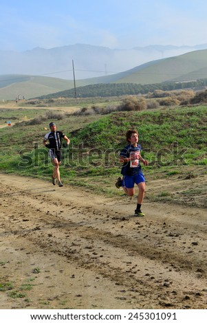 BAKERSFIELD, CA - JAN 17, 2015: Contestants run the first stage of the Rio Bravo Rumble biathlon (running and mountain biking) on a scenic dirt trail. - stock photo