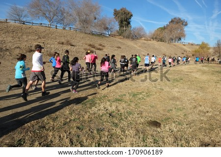 BAKERSFIELD, CA - JAN 11, 2014: The ten kilometer race contestants are sprinting off to a fast start at the 24th Annual Fog Run, although there is only abundant sunshine this year. - stock photo