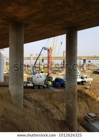 BAKERSFIELD, CA - JANUARY 29, 2018: Crane-supported pile drivers drill deep into the earth while concrete is pumped into steel column forms for the Kern River Bridge Improvements Project.