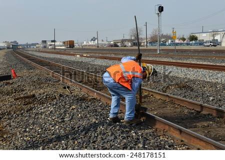 BAKERSFIELD, CA - JANUARY 29, 2015: Two Union Pacific Railroad employees position a tool on a rail to assist in replacing old wood tie with a new one. - stock photo