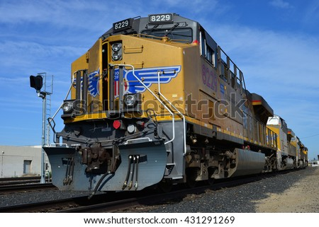 BAKERSFIELD, CA - JUNE 2, 2016: A powerful diesel electric locomotive displaying Union Pacific colors, with the crew door slightly ajar, rests in the yard awaiting its next assignment.