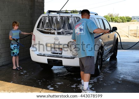 BAKERSFIELD, CA - JUNE26, 2016: Brian Daley and his son, Phillip, are devoting Sunday morning to washing their SUV at the local self-service car wash.