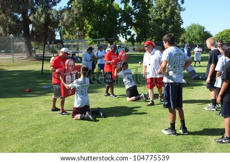 BAKERSFIELD, CA - JUNE 9: Coaches teach the fundamentals of the game to boys at the Golden Empire Youth Football Camp at Bakersfield Community College on June 9, 2012,  in Bakersfield, California. - stock photo