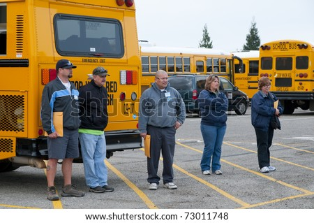 """BAKERSFIELD, CA - MAR 12: The 28th Annual School Bus """"Roadeo"""" tests driver skills on March 12, 2011, in Bakersfield, California. Drivers await their turn to compete. - stock photo"""