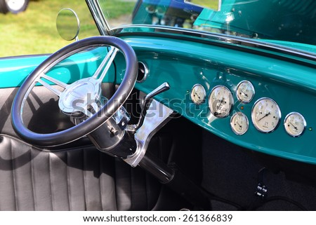 """BAKERSFIELD, CA - MARCH 14, 2015: A colorful Ford-based hot rod roadster is on display at the """"Cruisin' for a Wish"""" classic car show. The instrument panel  features a spartan, functional layout. - stock photo"""