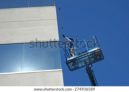 BAKERSFIELD, CA - MAY 2, 2015: A window washer works high off the ground on the platform of a man lift to wash the windows of a Kern County office building.