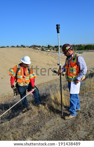 BAKERSFIELD, CA-MAY 7, 2014: Work is about 30% complete on the widening of State Route 178. David Oliveras (left) and Sam Espinosa are part of the survey crew staking lines and grades. - stock photo
