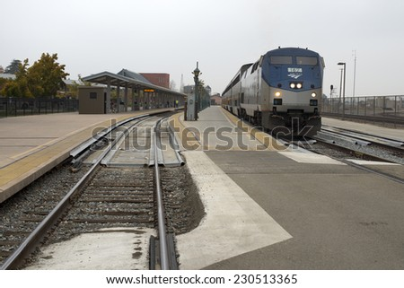 BAKERSFIELD, CA - NOVEMBER 14, 2014: An Amtrak California passenger train pulls out of the station heading north up the San Joaquin Valley to San Francisco. - stock photo