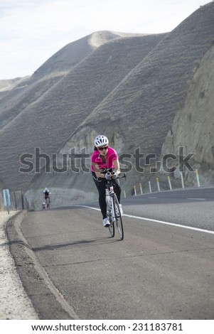 BAKERSFIELD, CA - NOVEMBER 16, 2014: An unidentified woman contestant in the Kern River Duathlon crests a steep and difficult hill while racing in the bicycling stage of the race. - stock photo
