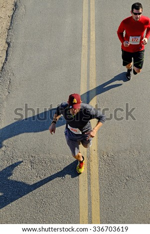 BAKERSFIELD, CA - NOVEMBER 7, 2015: Two contestants present an unusual top view as they run under an overpass during the 33rd Annual Bakersfield Police Department Memorial Run. - stock photo
