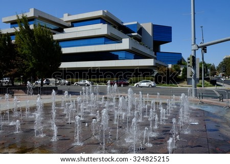 BAKERSFIELD, CA - OCTOBER 6, 2015: Viewed across the foreground fountain, the Kern County Administrative Center appears, rendered in the planes and sharp angles of modern architecture.