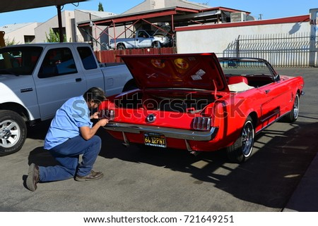 BAKERSFIELD, CA - SEPTEMBER 23, 2017: An unidentified mechanic at a specialty auto shop is carefully installing a new tail light for a classic 1964 Ford Mustang convertible.