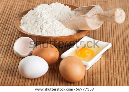 Bakery ingredient. Flour with raw eggs for making dough - stock photo